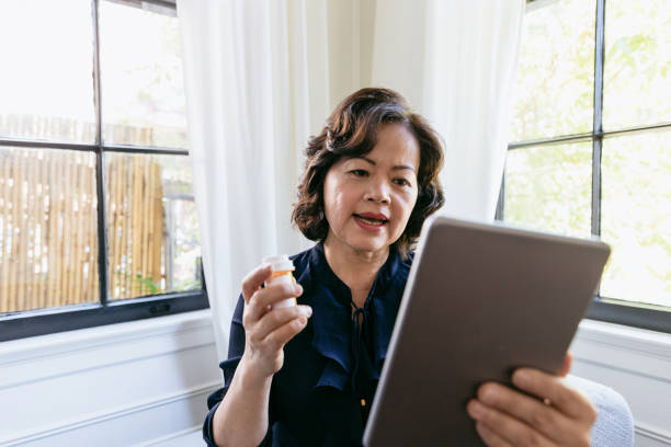 senior woman talks with a doctor online - telemedicine stock pictures, royalty-free photos & images