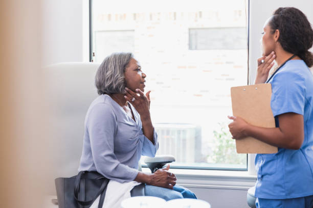 Senior woman talks with dermatologist A senior woman gestures toward her face while discussing a skin rash with a female dermatologist. dermatologist stock pictures, royalty-free photos & images