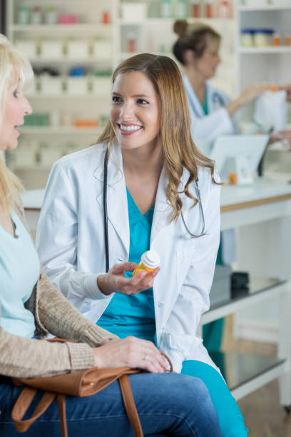 senior woman talks with pharmacist about medication side effects - pharmaceutical compounding stock photos and pictures