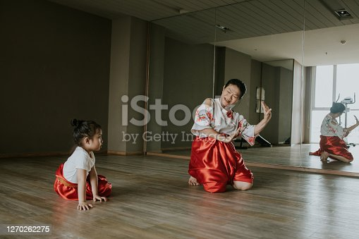 Thai grandmother teaching her little kid for learning Thai traditional dancing at the gym, Bangkok Thailand