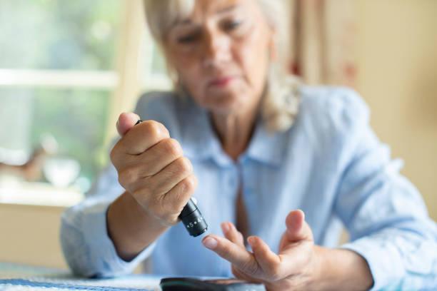 Senior Woman testet Blutzuckerniveau zu Hause – Foto