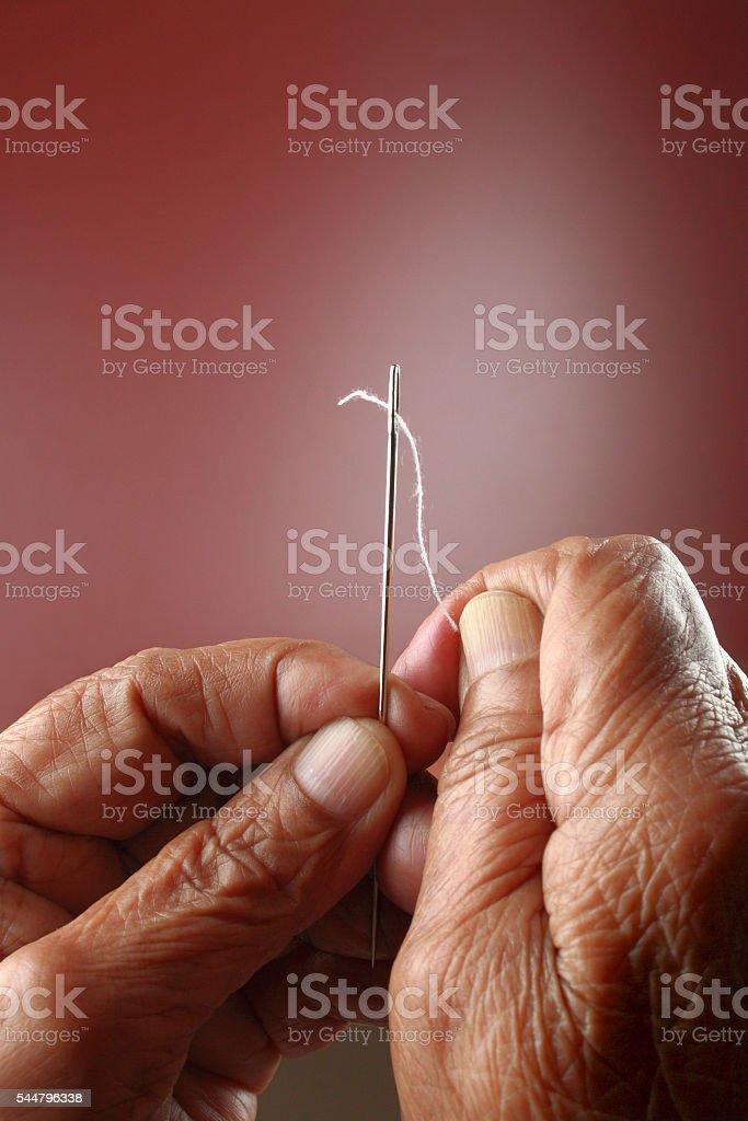 Senior woman threading the needle stock photo