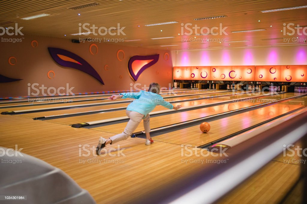 One senior woman bowling with her friends. She has just thrown the...