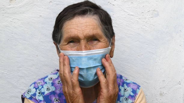 Senior woman touch disposable mask on her aged face with deep wrinkles on her forehead and near eyes stock photo