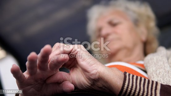 698466046istockphoto Senior woman touching her injured hand sitting on porch swing, suffering pain concept, cinematic dof 1158835003
