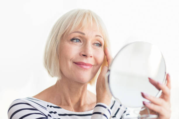 Senior woman touching her soft face skin Senior woman touching her soft face skin, looking in mirror at home aging stock pictures, royalty-free photos & images
