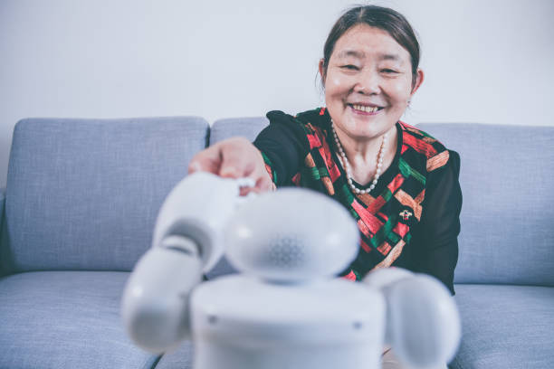 Senior woman touching robot finger indoors stock photo