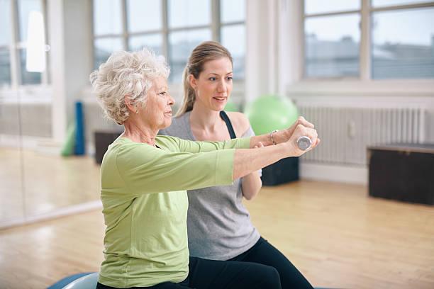 Senior Frau training im Fitnessraum mit einem personal trainer – Foto