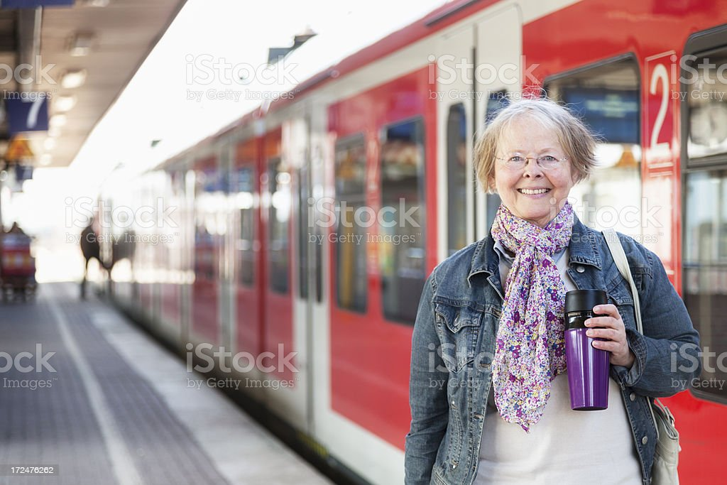 senior woman traveling with train on platform royalty-free stock photo