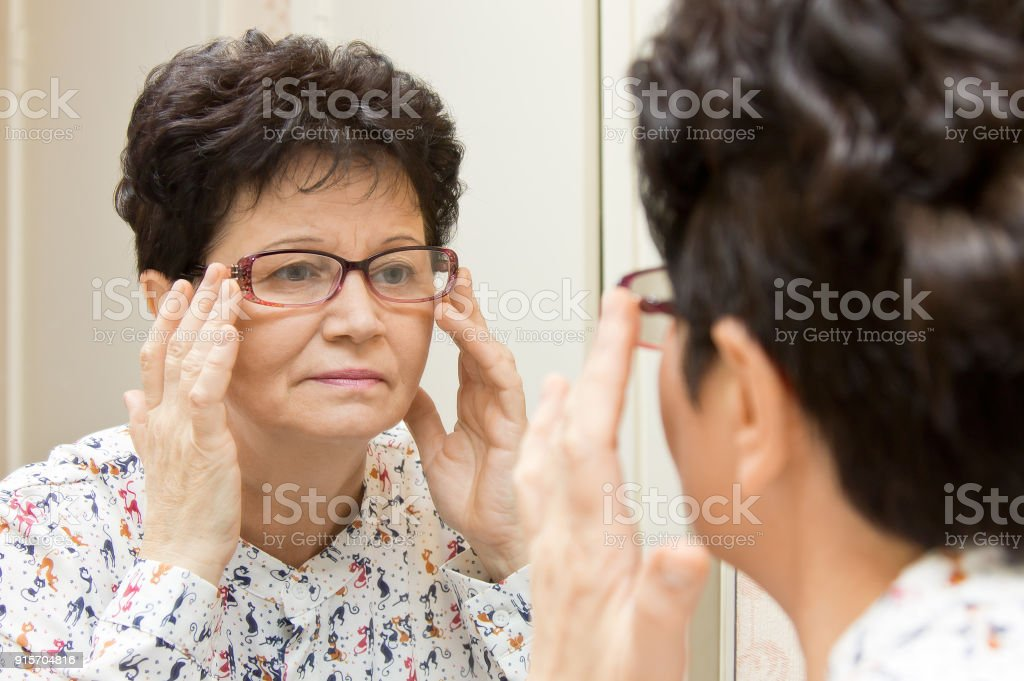 Senior Woman Trying On New Glasses And Looking In The Mirror Stock