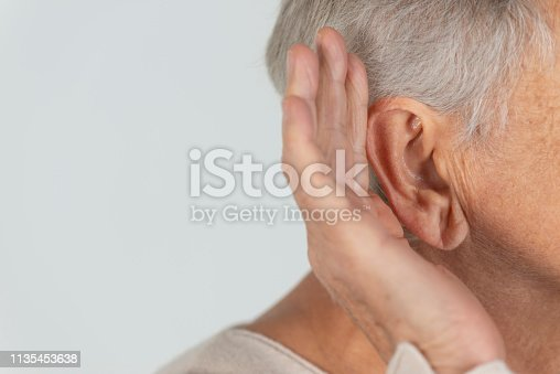 Senior woman trying to hear, gray background.