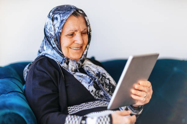 senior woman using a digital tablet - скромная одежда стоковые фото и изображения
