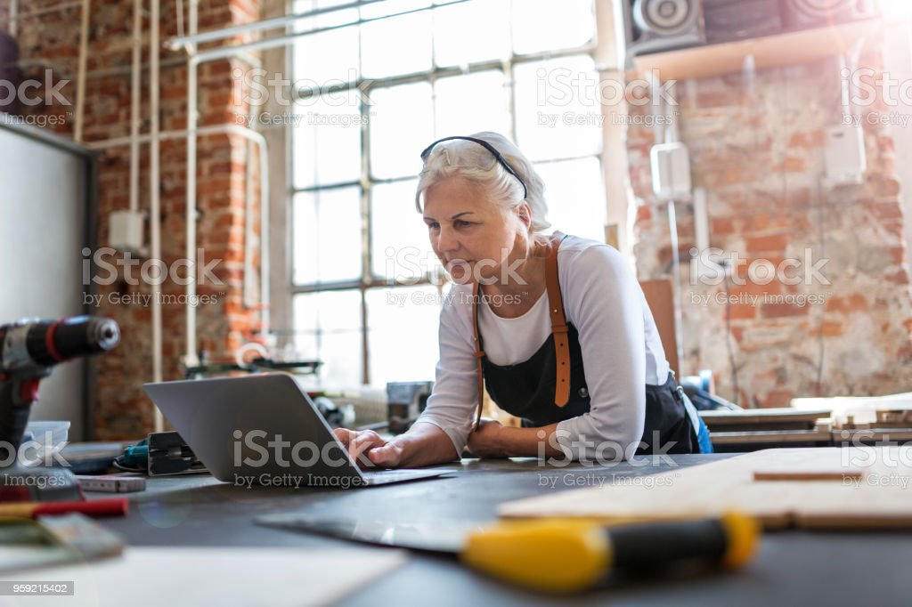 Senior woman using a laptop in a workshop stock photo