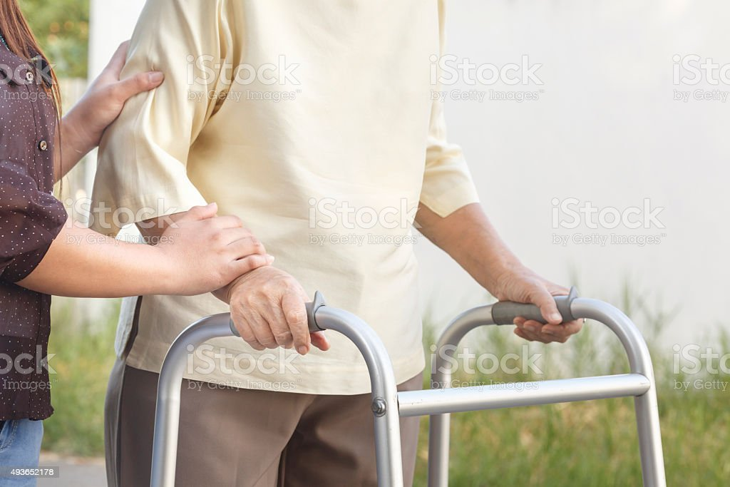 senior woman using a walker with caregiver stock photo