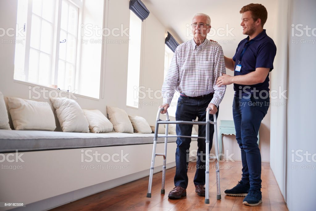 Senior woman using a walking frame with male nurse at home stock photo
