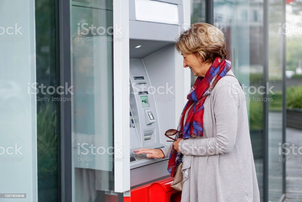 Senior woman using ATM in the city stock photo