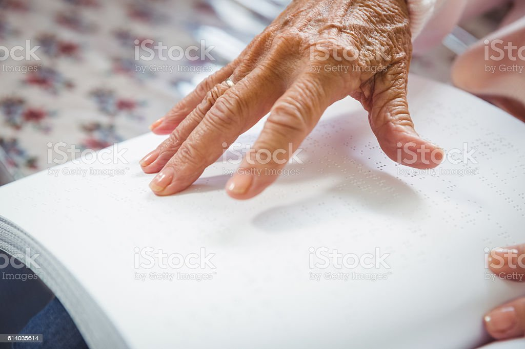 Senior woman using braille to read stock photo