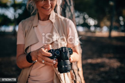 istock Senior woman using camera and looking at photos in nature 979294778