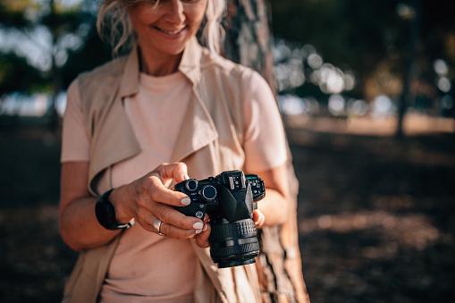 Senior woman using camera and looking at photos in nature
