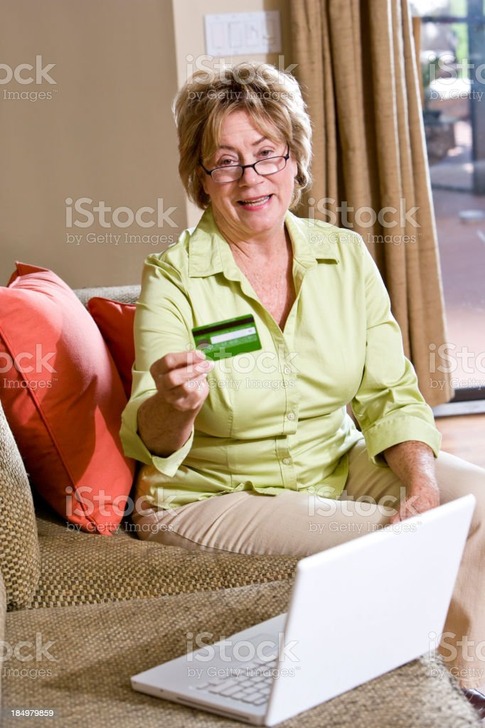Senior woman using creditcard to shop online with laptop stock photo