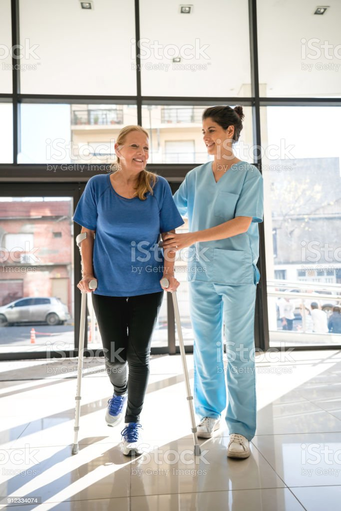 Senior woman using crutches coming into the clinic for physiotherapy and therapist helping her stock photo