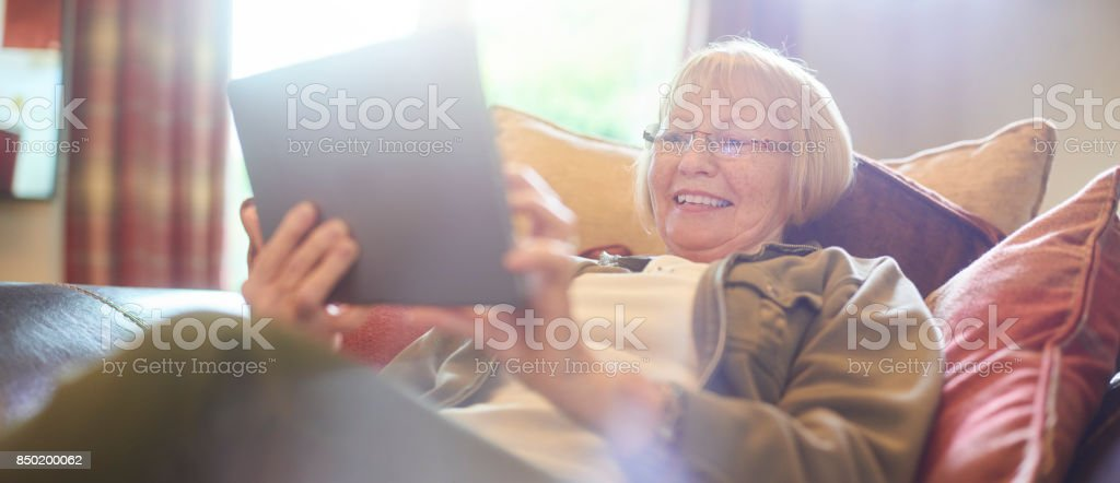 senior woman using digital tablet at home stock photo