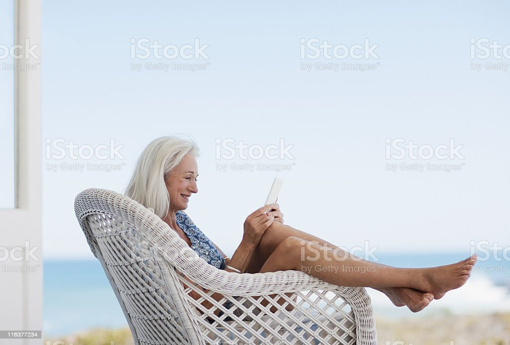Senior woman using digital tablet in chair stock photo