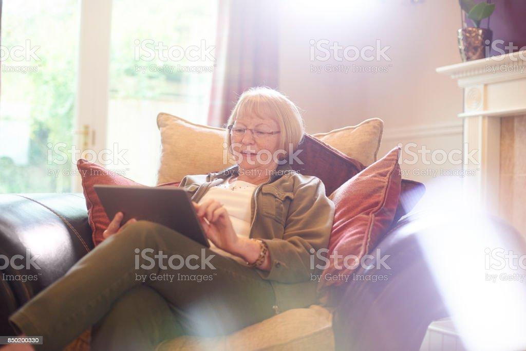 senior woman using digital tablet stock photo