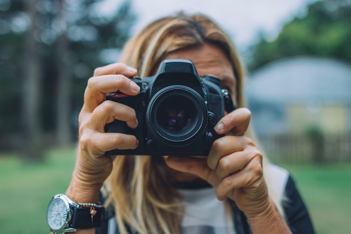 Senior woman using DSLR camera