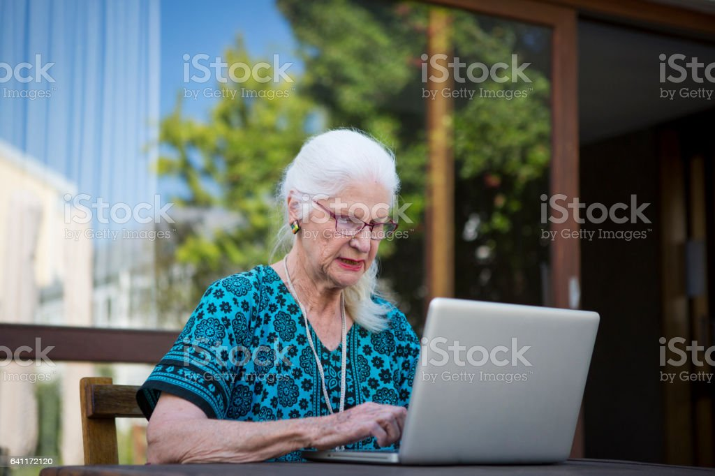Senior Woman using her laptop outside stock photo