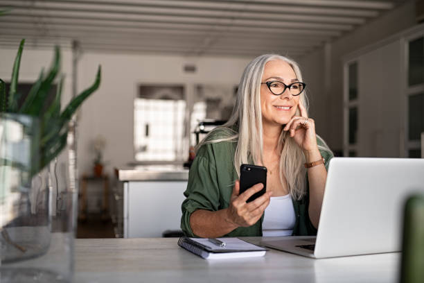 Senior woman using laptop and smartphone Happy senior woman holding smartphone and laptop daydreaming while looking away. Successful stylish old woman working at home while thinking about a good future. Cheerful fashionable lady entrepreneur wearing cool eyeglasses. banking stock pictures, royalty-free photos & images