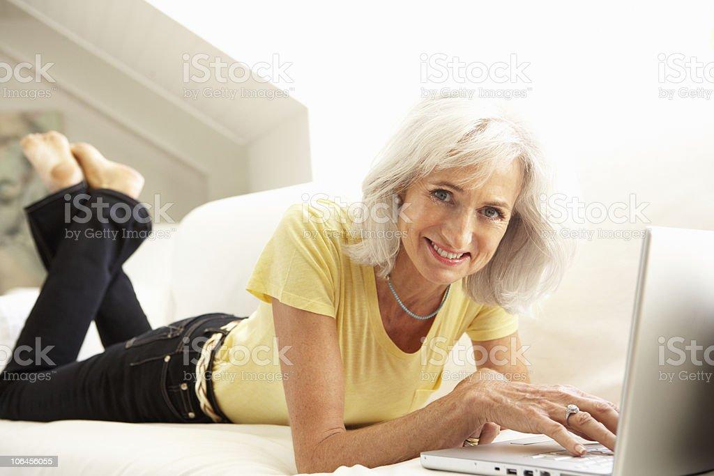 Senior Woman Using Laptop Relaxing On Sofa royalty-free stock photo