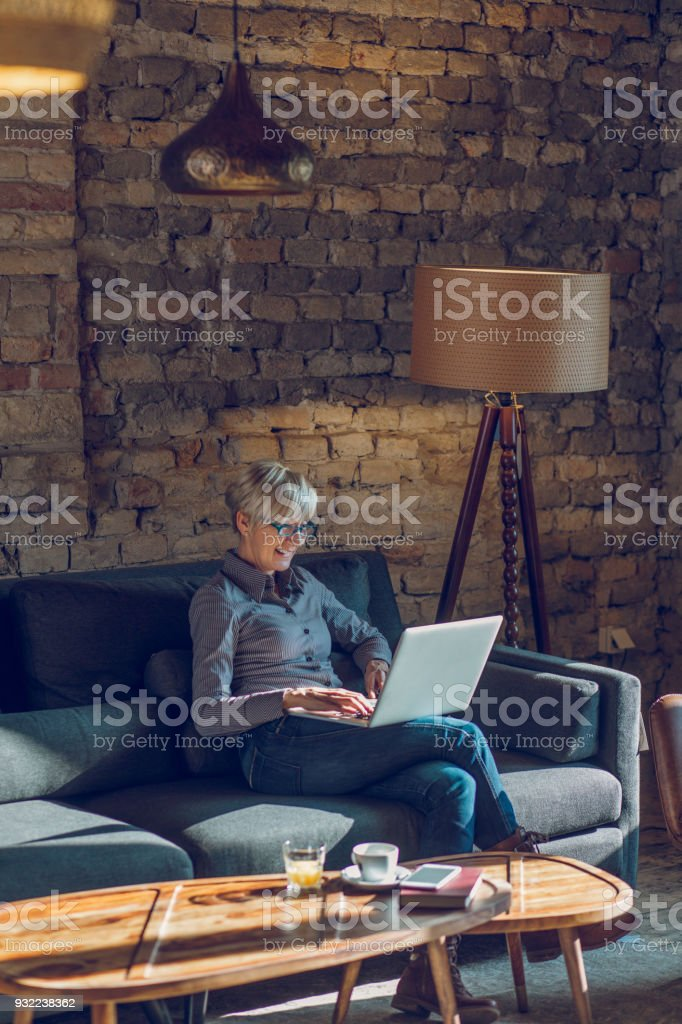 Senior woman using laptop while relaxing at home stock photo