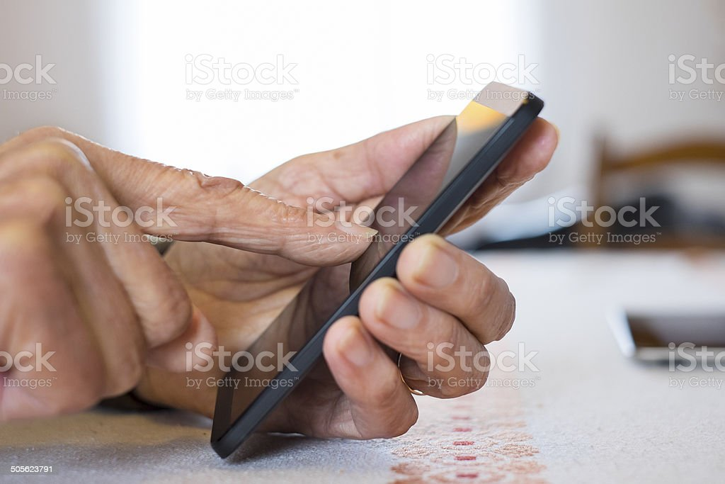 Senior woman Using mobile phone at home stock photo