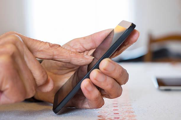 Senior Frau mit Handy zu Hause – Foto