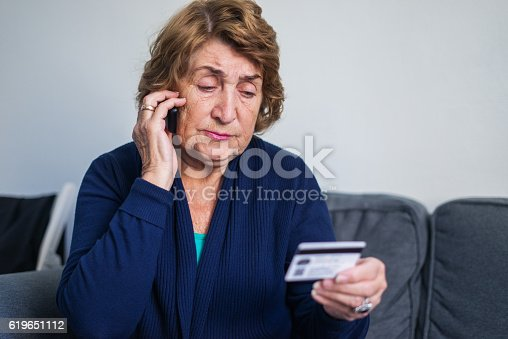 istock Senior woman using mobile phone while holding credit card 619651112