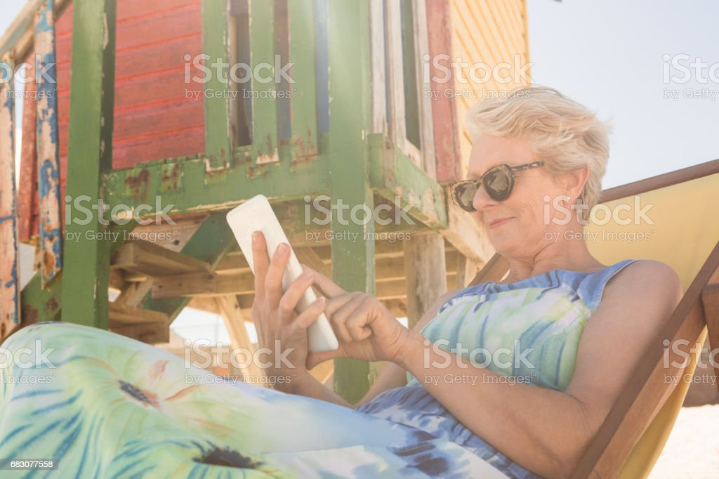 Senior woman using mobile phone while sitting on chair foto de stock royalty-free