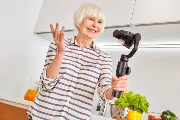 senior woman using modern smartphone, standing in kitchen at home - dodatkowa praca zdjęcia i obrazy z banku zdjęć