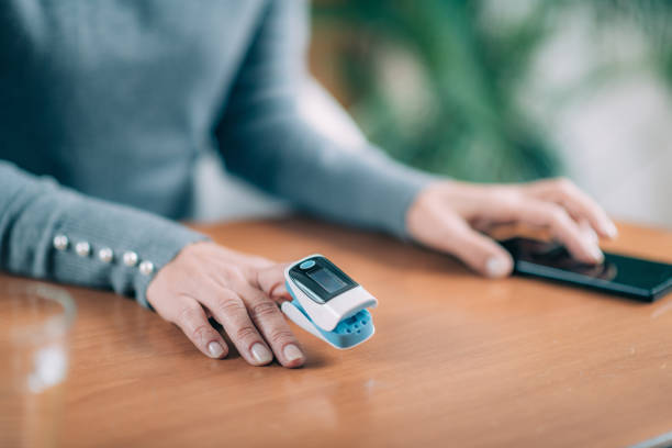 Senior Woman Using Pulse Oximeter and Smart Phone, Measuring Oxygen Saturation stock photo