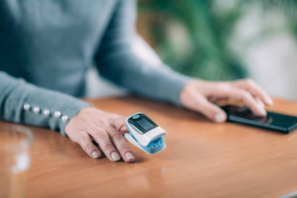 Senior Frau mit Pulsoximeter und Smart Phone, Messung der Sauerstoffsättigung – Foto