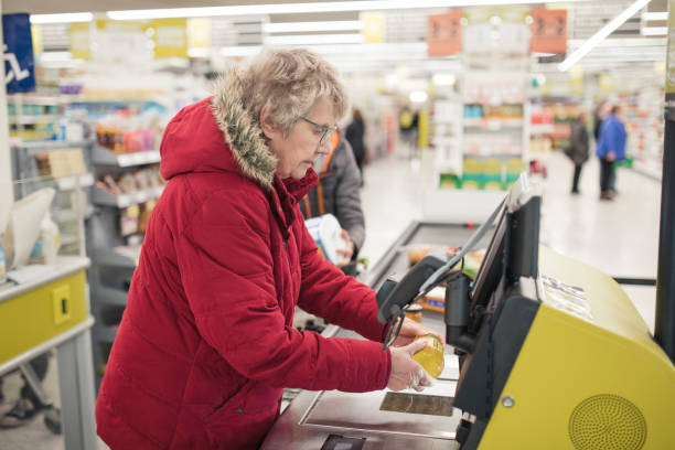 senior woman using self service checkout - day in the life series stock pictures, royalty-free photos & images