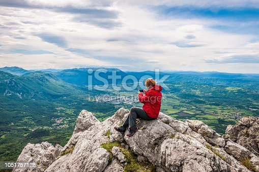 Senior woman using phone up in the mountains, Slovenia, Europe. All logos removed. NIKON D3X, 24.0-70.0 mm f/2.8.
