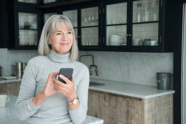 senior woman using smartphone in modern kitchen - vrouw 60 stockfoto's en -beelden
