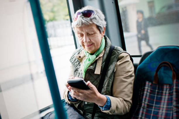 Senior woman using smartphone in the bus stock photo