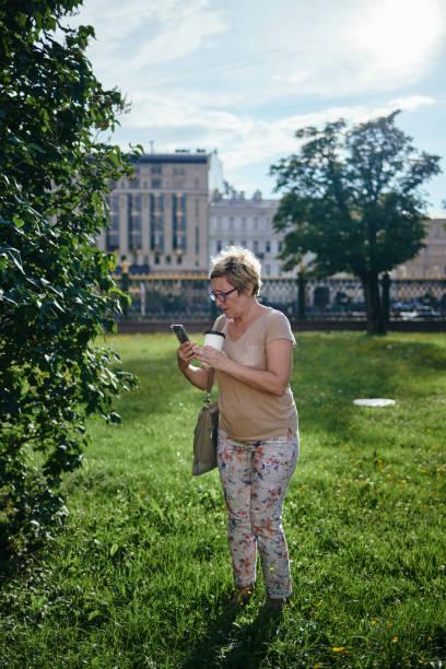 Senior woman using smartphone near bush stock photo