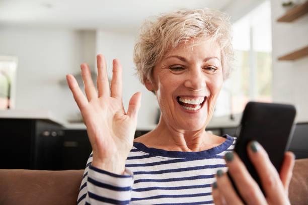téléphonie vidéo femme senior sur smartphone à la maison, gros plan - seulement des femmes seniors photos et images de collection