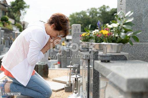 Senior woman visiting family grave