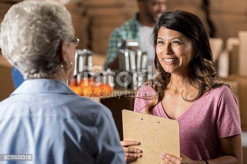 istock Senior woman volunteers at food bank 623503318