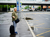 Senior woman waiting for taxi on the street