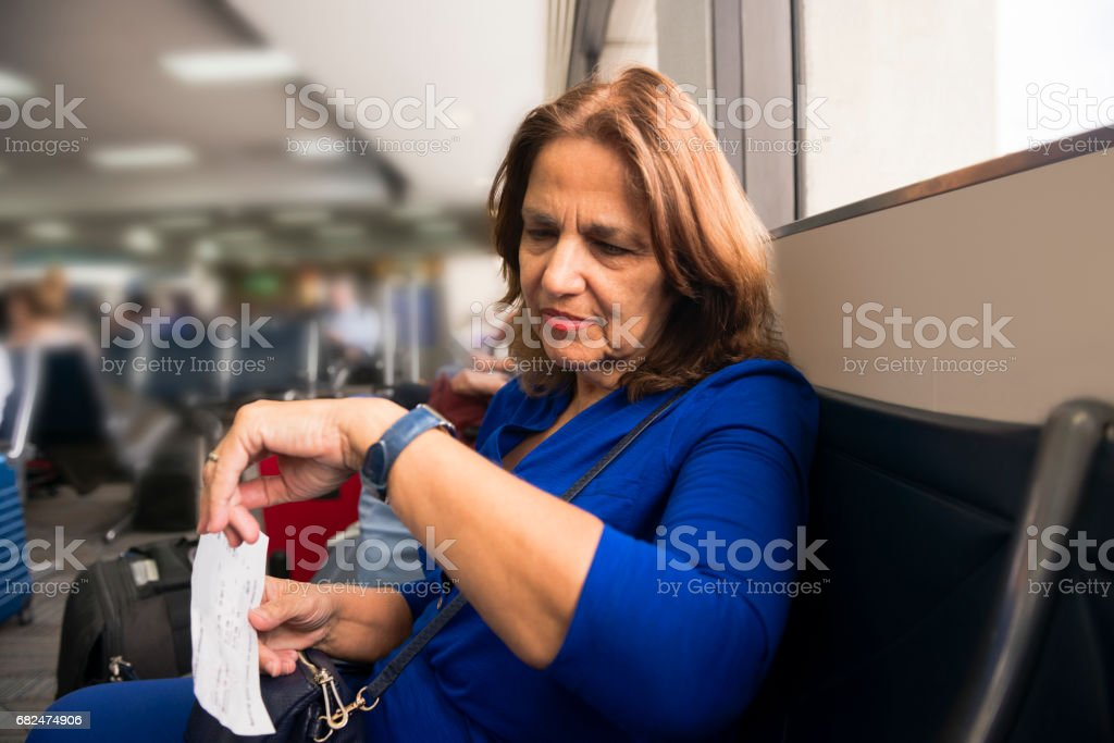 Senior Woman Waiting in the Airport Checks Time on Watch foto stock royalty-free